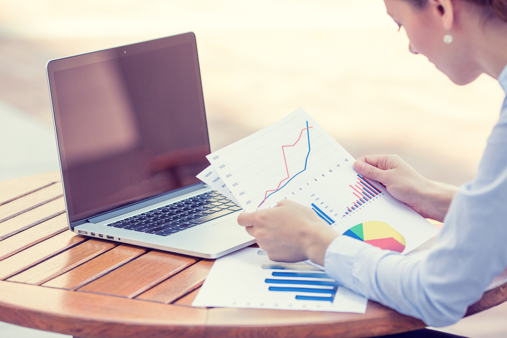 woman investment consultant analyzing company annual financial report balance sheet statement working with documents graphs. Stock market, office, tax, education concept. Hands with charts papers-1